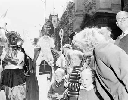 """St Nicholas visited Australia - to the delight of thousand of Dutch and Australian born children this month (December). Accoompanied by """"Black Peters"""" a band, mounted police and Dutch people in national dress, he rode on white horse along Swanston Street - one of the main streets of Melbourne, Australia's second biggest city and capital to Victoria - to call on the Lord Mayor, Councillor Leo Curtis, at the Melbourne Town Hall, on December 3. Dutch migrants in national dress accompanying St Nicholas to the Melbourne Town Hall. From the National Archives of Australia. 7428245"""